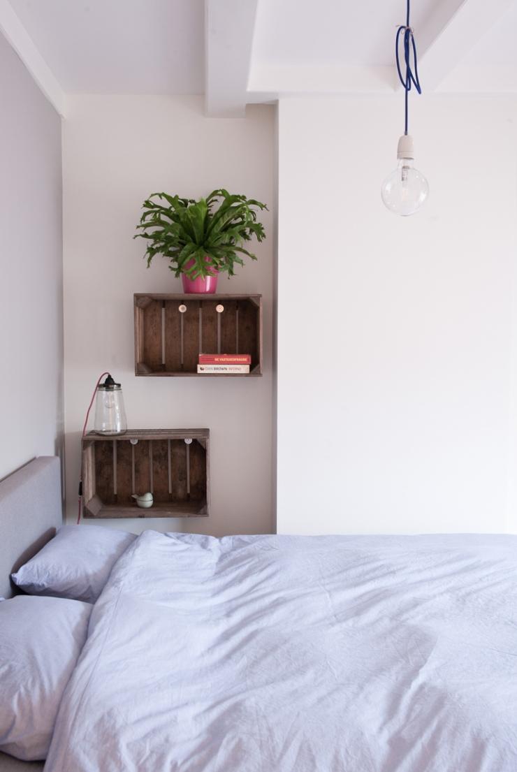Naast het bed hangen houten kratjes, ideaal om boeken in op te bergen. De lamp is van I am Recycled.