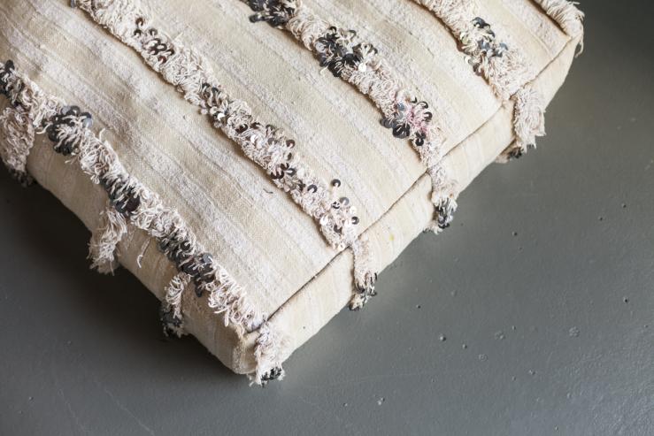 De kussen op de grond is een handgemaakt Marokkaans kussen van Stylenoot,