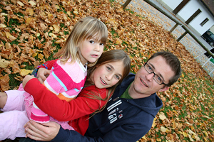 father with his two daughters sitting in a park in autum leaves